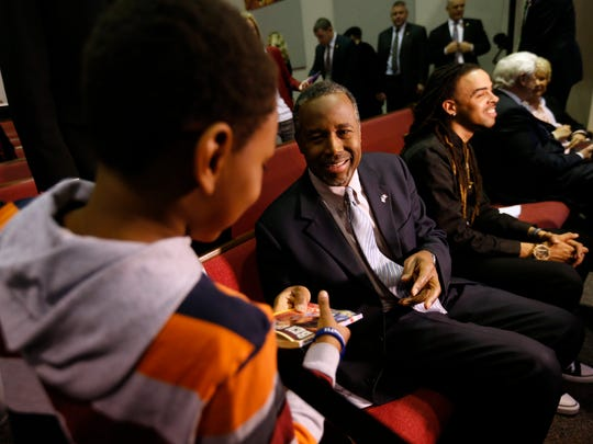 Republican presidential candidate Ben Carson signs a copy of his autobiography for James Merritt, 8, at 7:16 p.m. Tuesday, Jan 26, 2016, at Heritage Assembly of God in Des Moines.