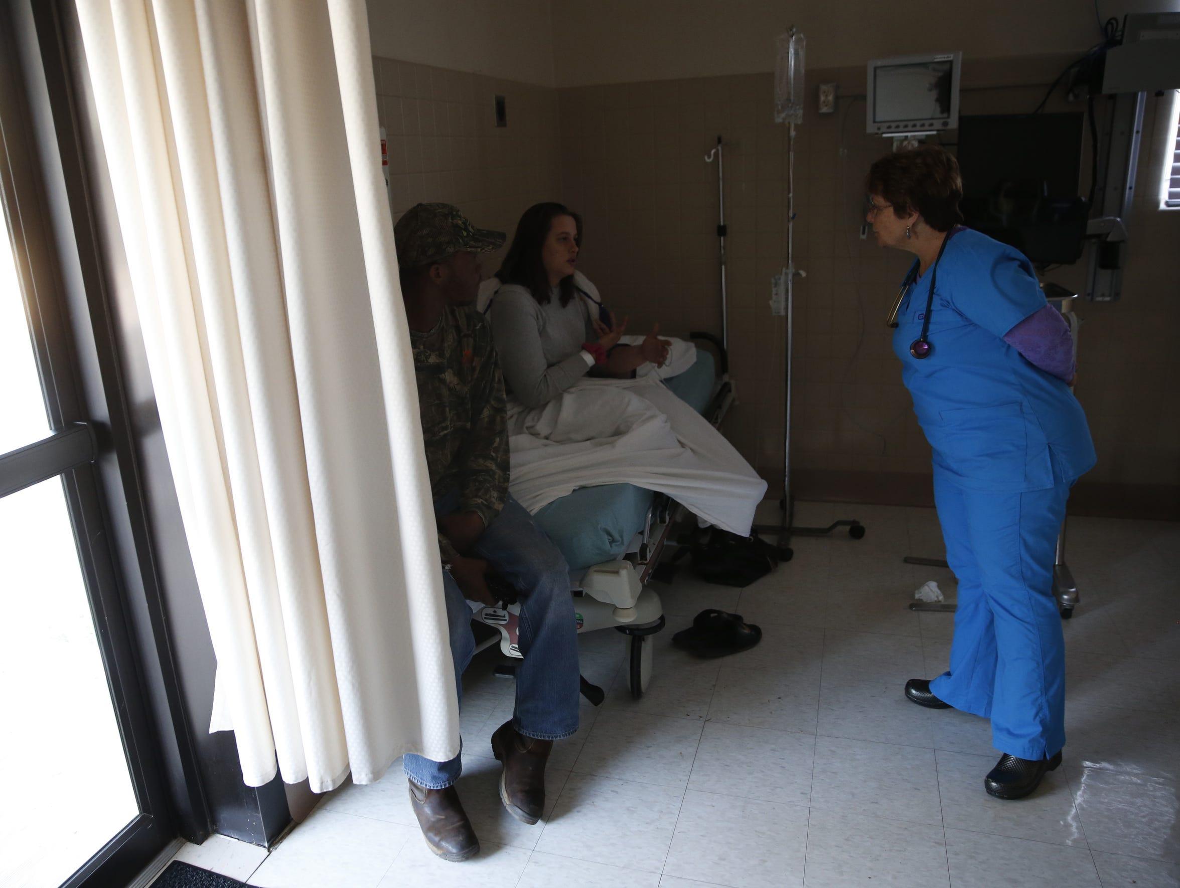 Nurse Ester Stoltzfus speaks to a patient in the dimly