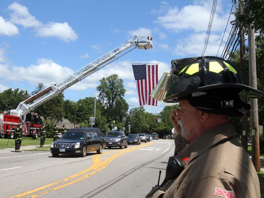From left, East Fishkill and Dutchess Junction firefighters salute as the procession for U.S. Marine Corps Gunnery Sgt. Brendan Johnson travels along Rt. 52 in Fishkill after arriving from Dover Air Force Base July 26, 2017. Johnson was among 15 Marines and one Navy corpsman killed when the aircraft they were in crashed in Mississippi.