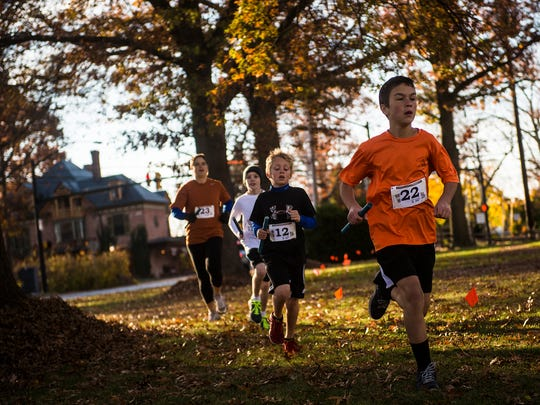 Runners pass under the trees with the relay baton on Nov. 8 in Gettysburg as part of the Adams County XC race.