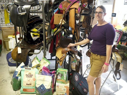 """Corner Stable Tack Shop owner Whitney Hanford arranges inventory in her new shop at 34 N. 16th Street in Lebanon, has brought the country to the city. Owner Whitney Hanford opened the doors in mid-May meeting equestrian needs from mini to draft horses. The shop carries equipment for English, western dressage and endurance. The operation can custom-make tack (halters, bridles, etc.) for hard-to-fit equines. """"People are finding us,"""" Hanford said of her small shop in the former Printed Terry Building. Hanford said 70 percent of the items she carries are American made. Hanford also noted that on Fridays, 5 percent of sales go to benefit CATRA, the Capital Area Therapeutic Riding Association, which is a nonprofit organization providing therapeutic horseback riding to people with disabilities."""