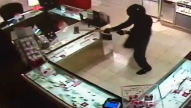 Helmeted robber chops an ax into a jewelry case at the Macy's at Glendale Town Center.
