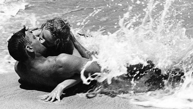 """The surf crashes as Sgt. Warden (Burt Lancaster)  and Mrs. Holmes (Deborah Kerr) lock lips in """"From Here to Eternity."""""""
