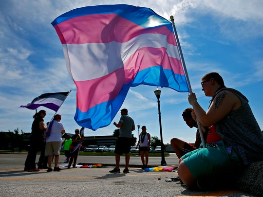 Flag bearer Scott Young holds the transgender Pride flag prior to the start of the Equality March as part of the 2016 Greater Ozarks Pridefest in Springfield, Mo. on June 17, 2016.