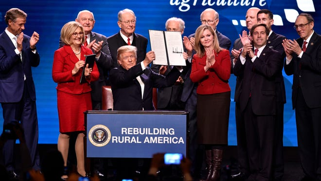 President Donald Trump holds an executive order on rural broadband flanked by the Tennessee delegation and other dignitaries at Gaylord Opryland Resort & Convention Center Monday, Jan. 8, 2018 in Nashville, Tenn.