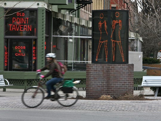 "A bicyclist rides past ""Ann Dancing"" at the intersection of Massachusetts Avenue, Vermont and Alabama Streets, on the Indianapolis Cultural Trail."