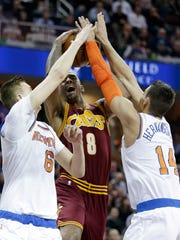 Cleveland Cavaliers' Channing Frye (8) is stopped by New York Knicks' Kristaps Porzingis (6), from Latvia, and Willy Hernangomez, from Spain, in the first half of an NBA basketball game, Thursday, Feb. 23, 2017, in Cleveland. (AP Photo/Tony Dejak)