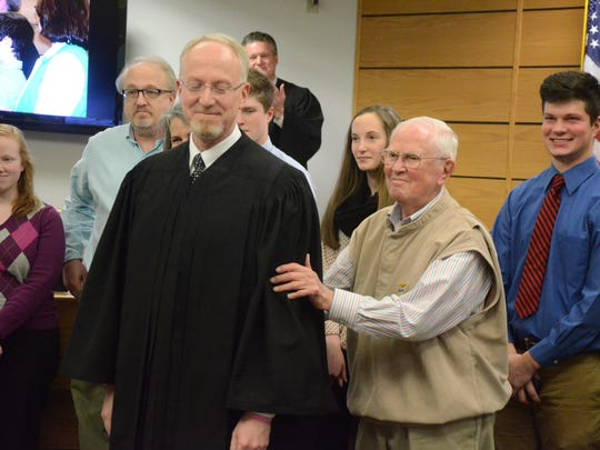 Circuit Judge John Hallacy is given a pat by his father,