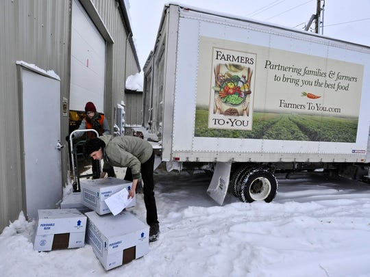 Joseph Ferris and Rachel Ries prepare to load foods grown and produced in Vermont for delivery to customers in Boston at Farmers To You in Berlin on Tuesday.