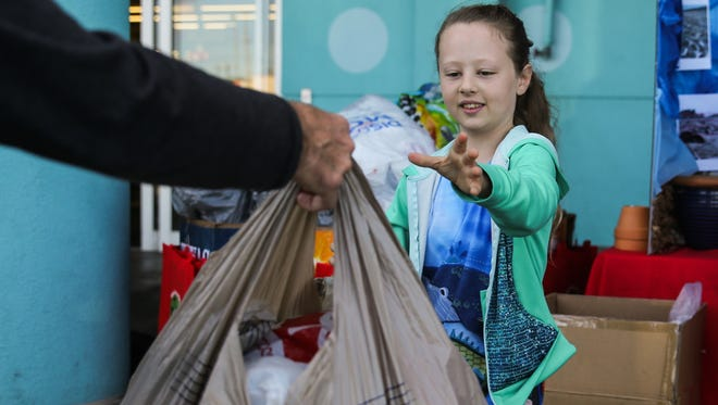 Ella Elkins, 8, takes plastic bags from a customer during her recycling event Saturday, Feb. 24, 2018, at H-E-B in San Angelo.