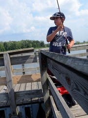 Eric Compton, 12, of Port Huron, reels in his line Monday, Aug 17, at 40th Street Pond.