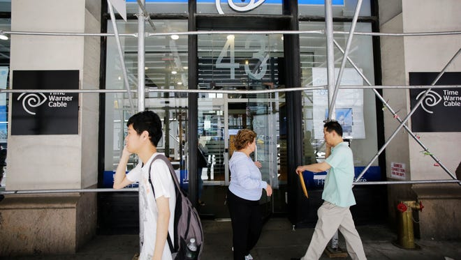 People shop at a Time Warner Cable store, on May 26, 2015, in New York. Charter Communications is buying Time Warner Cable for $55.33 billion. And executives say they're confident regulators will allow the creation of another U.S. TV and Internet giant.