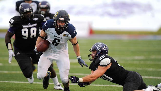 Northern Arizona University running back Casey Jahn (6) slips past Abilene Christian linebacker Justin Stephens (20) during the an NCAA college football game, Saturday, Sept. 6, 2014, at Shotwell Stadium in Abilene, Texas.