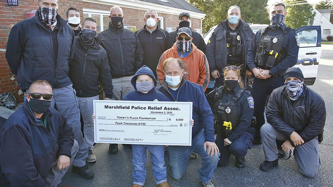 "Young Danny Sheehan,7 of Marshfield who is battling cancer receives a $4k check from the Marshfield Police Relief Association for ""Tommy's Place"" a family retreat in Falmouth for families of ill children on Monday November 2, 2020  Greg Derr/ The Patriot Ledger"