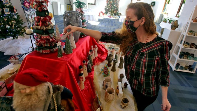 Violet Dukes arranges one of many displays featuring handmade items for sale this holiday season at the Cleveland County Arts Council.