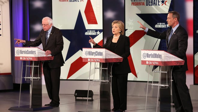 Bernie Sanders, left, Hillary Clinton and Martin O'Malley gesture as they speak during a Democratic presidential debate at Drake University in Des Moines on Saturday, Nov. 14, 2015.