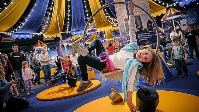 """Elaine Hemmert strikes a pose on a Lyra, or an aerial ring, at the new """"Circus--Starring YOU!"""" exhibit at the Children's Museum of Indianapolis."""