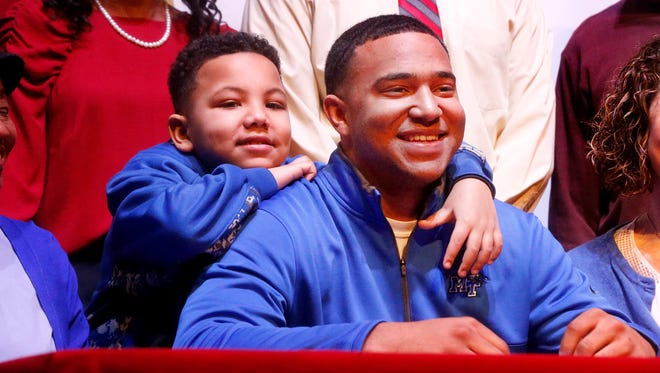 Riverdale football player Jarek Campbell gets ready to sign a letter of intent Wednesday to play football at MTSU. His younger brother Elijah Chestnutt, 7, hangs over his shoulder as family pictures are taken.