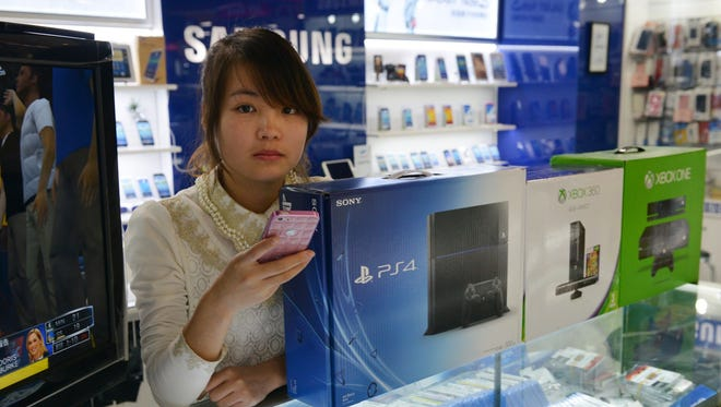 A Chinese vendor sells game consoles. including Xbox One and Sony's PS4, back in January. They are said to enter China through unofficial channels.