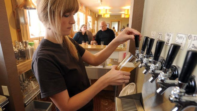 Maddie Johnson pours a beer for customers at High Hops during the Windsor brewery's opening day on Oct. 19, 2012.