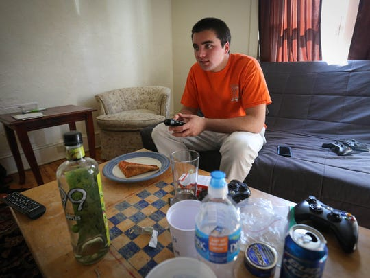University of Delaware senior Joe Moye watches television Wednesday in the living room of his Prospect Avenue rental home in Newark. City inspectors are tasked with checking on the conditions of rental properties.