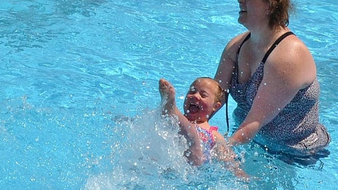 In this file photo from several years ago, Alexis Rosenfeldt, 5, happily splashes in the Aageson Pool in Oconto with a little help from her mother, Rachel Rosenfeldt.