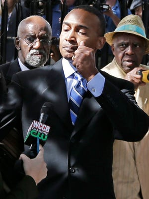 Former Charlotte Mayor Patrick Cannon, right, leaves the federal courthouse Oct. 14, 2014, in Charlotte, N.C., after being sentenced to 44 months in prison.