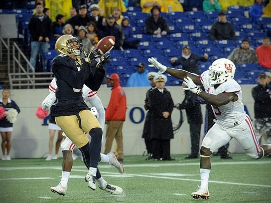 Navy wide receiver Brandon Colon beats two Houston defenders to haul in pass that went for a touchdown on Saturday, Oct. 8, 2016 at Navy-Marine Corps Memorial Stadium in Annapolis.