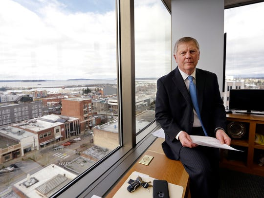 In this Feb. 16, 2017, photo, Everett Mayor Ray Stephanson sits in his corner office overlooking downtown Everett, Wash. Stephanson is suing pharmaceutical giant Purdue Pharma, becoming the first city trying to hold the maker of OxyContin accountable for damages to his community. (AP Photo/Elaine Thompson)