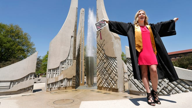 Kirsten Johnson wears the gown from her late mother, Kathy Johnson, Thursday, May 10, 2018, on the campus of Purdue University. Johnson is graduating with a degree in human services and minors in psychology and women's studies from Purdue. When she marches in Purdue's graduation ceremony this weekend, Johnson will be wearing the same gown her mother wore when she graduated from Roosevelt University.