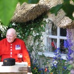 A British veteran sits outside a cottage at a garden show in England.
