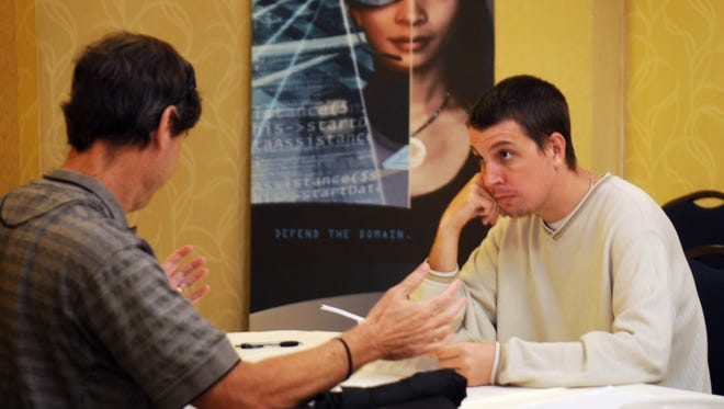 At left, Jonathan Cyr of Melbourne talks with Ladd Harris, a cyber software engineer at Raytheon during the job interview process at the Raytheon Job Fair held Friday at the Hilton Melbourne Beach Oceanfront.