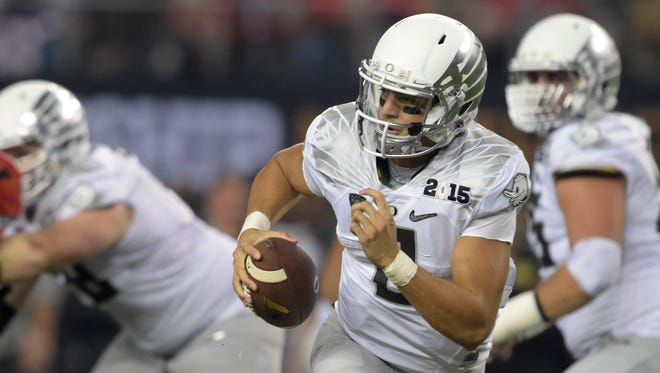 Jan 12, 2015; Arlington, TX, USA; Oregon Ducks quarterback Marcus Mariota (8) runs the ball during the second quarter against the Ohio State Buckeyes in the 2015 CFP National Championship Game at AT&T Stadium. Mandatory Credit: Kirby Lee-USA TODAY Sports