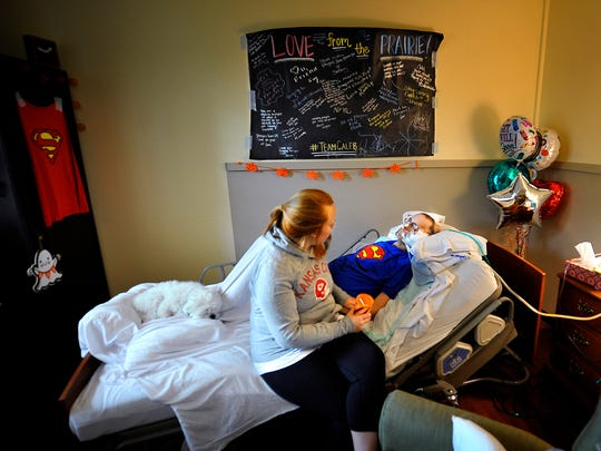 "Bethany Hanby enjoys some quiet time with her new husband, Caleb, at his bedside at Alive Hospice. Their dog, KC, lies on Caleb's feet at the end of the bed. Caleb's mother, Michelle, said he's wearing the Superman shirt ""because he's our hero. He's fighting so hard."""