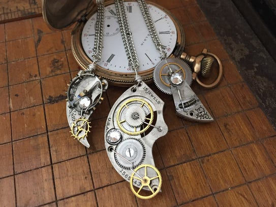 Three pendants lay over a pocket watch at Steenhagen