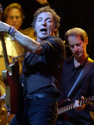 Bruce Springsteen, center, is pictured with E Street Band drummer Max Weinberg, left, and bassist Garry Tallent, with he respectively has played 42 and 46 years.