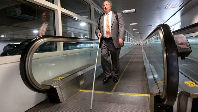 Fred Wurtzel of Lansing uses the moving walkway at the Detroit Metropolitan Wayne County Airport at the  McNamara terminal in Romulus, after arriving at the airport's ground transportation area that was recently moved on Wednesday, September 9, 2015. Wurtzel, past president of the National Federation of the Blind doesn't like the changes the airport made for those using public ground transportation.