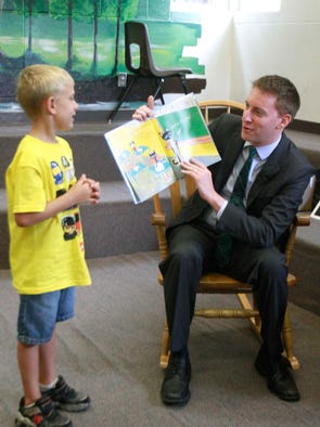 "Clayton McLaughlin, 6, helps out Jason Kander, Missouri Secretary of State, as he reads the book ""Pete the Cat"" to children at  at Bingham Elementary School as part of Kindergarten Camp on Tuesday, July 8, 2014."