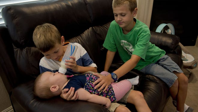 Simon Hinson, 7, feeds his sister Lucy, 6 months, as brother Justin, 10, looks on in Lincoln, Calif., in September 2014.