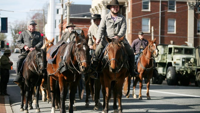 Civil War era reenactors accompany a horse team that is pulling a cannon in Staunton's annual Veterans Day parade on Saturday, Nov. 8, 2014.