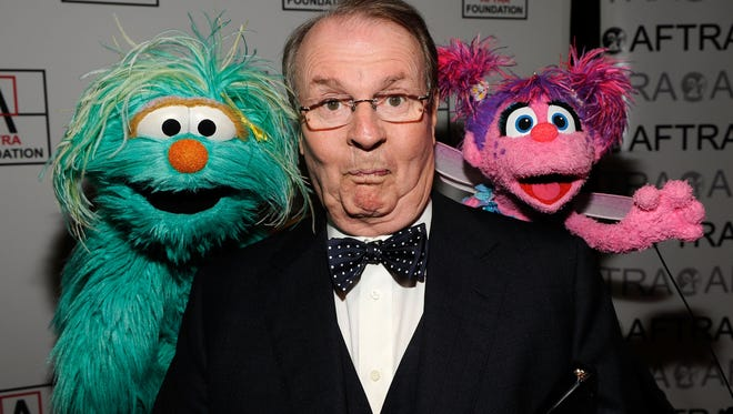 "TV personality Charles Osgood poses with Sesame Street characters at the 2010 AFTRA AMEE Awards. He announced on Sunday that he will be stepping down as host of ""CBS Sunday Morning"" after 22 years."