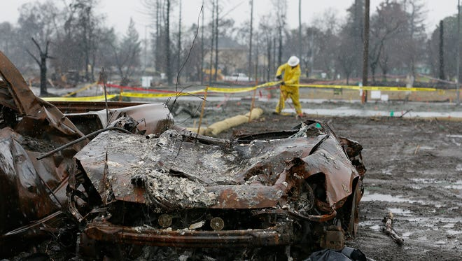 With a burned car in the foreground a worker finishes up erosion control efforts in the wildfire damaged Coffey Park neighborhood, Monday, Jan. 8, 2018, in Santa Rosa, Calif.