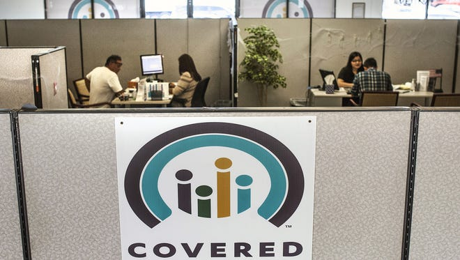 Insurance agents help sign people up for insurance through the Covered California exchange at their storefront in Huntington Beach on Nov. 1, 2016.