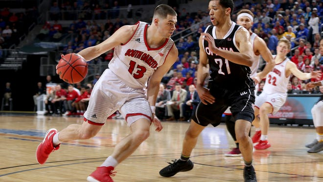 USD's Matt Mooney drives to the basket while guarded by Omaha's Zach Jackson #21 at the 2018 Summit League Basketball tournament at the Denny Sanford Premier Center in Sioux Falls. (Photo by Dick Carlson/Inertia)