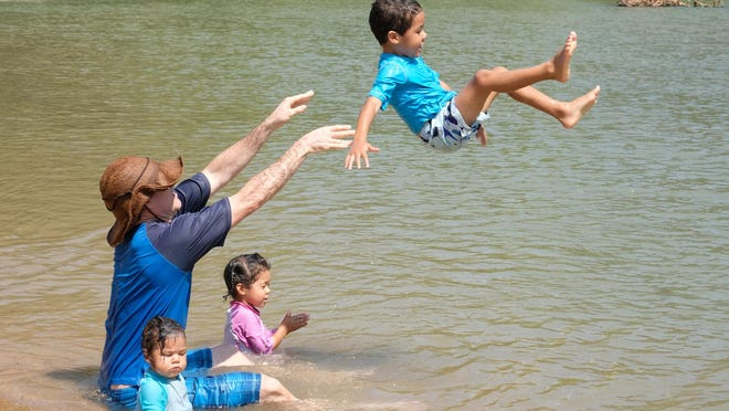 Bradley Lingold tosses his son, Shield, into the water after much begging from his son. His daughters, Peace, left, and Scepter, cool off in the Colorado River at Fisherman's Park in Bastrop on Friday when temperatures soared above 100 degrees. Triple-digit temperatures will continue over the weekend, forecasters say.