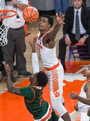Clemson forward Donte Grantham (32) blocks a shot by Miami sophomore Dewan Huell(20) during the second half at Littlejohn Coliseum in Clemson on Saturday.