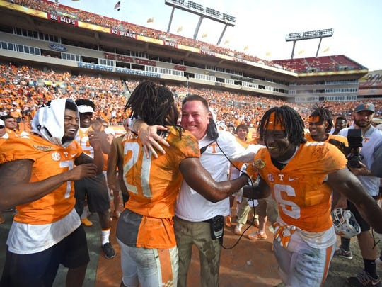 Tennessee head coach Butch Jones hugs linebacker Jalen Reeves-Maybin (21) after defensive back Cameron Sutton (7), Maybin and running back Alvin Kamara (6) doused him with Gatorade during Tennessee's 45-6 win over Northwestern in the Outback Bowl in Tampa, Fla., on Jan. 1, 2016.