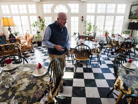 Larry Davis, one of the owners and innkeepers at the Willard Street Inn in Burlington, shows the dining area and solarium on Tuesday, January 9, 2018.