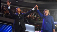 President Barack Obama and Hillary Clinton stand on