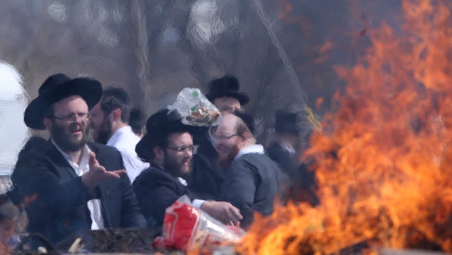 A man tosses bread into the fire as the Spring Valley Jewish community gather at Memorial Park to burn chametz or leavened products on the morning before Passover, April 10, 2017.